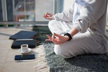 Mulher branca meditando na varanda em pijama antes de trabalhar, com tablet e celular